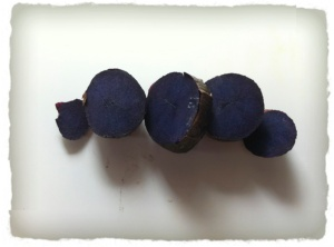 A small, cooked (roasted), purple potato that has been sliced.