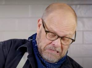Alton Brown making a grimacing face while wrangling his mixer
